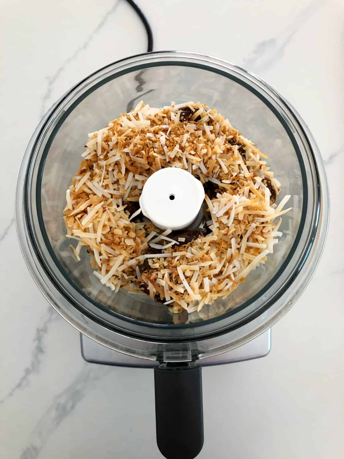 Toasted coconut and pitted Medjool dates in food processor on white marble.