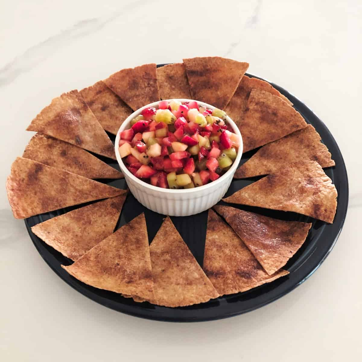 Fruit salsa in white bowl on platter scatter with cinnamon-sugar crisps.