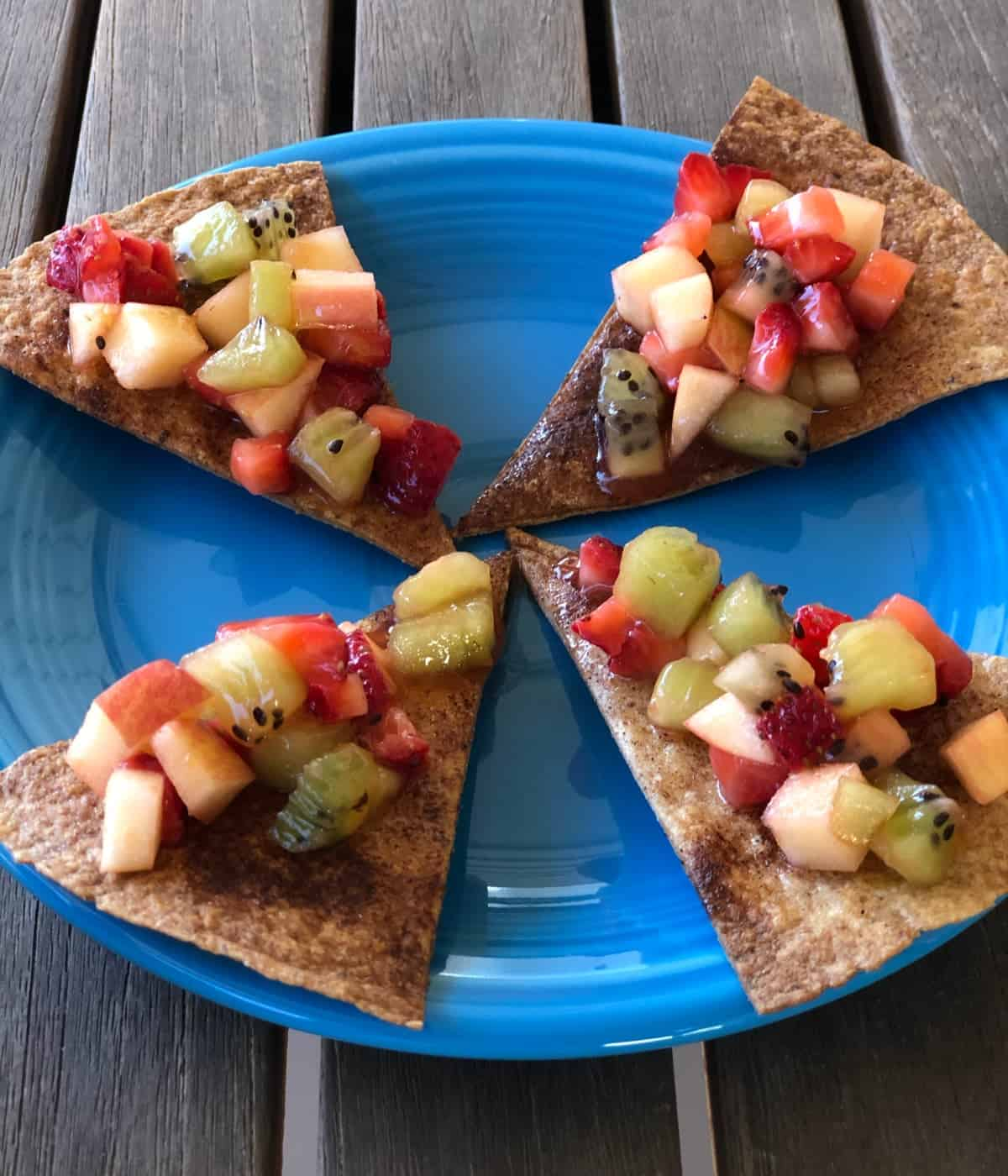 Four cinnamon-sugar crisps topped with fruit salsa on blue plate.
