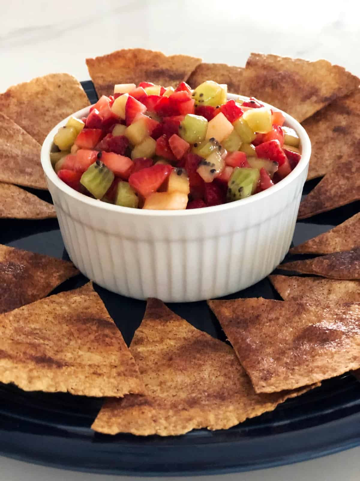 Cinnamon sugar crisps on platter with fruit salsa in white ramekin in center.