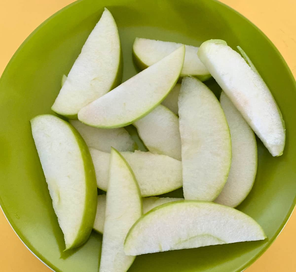 Granny Smith apple slices on green plate.