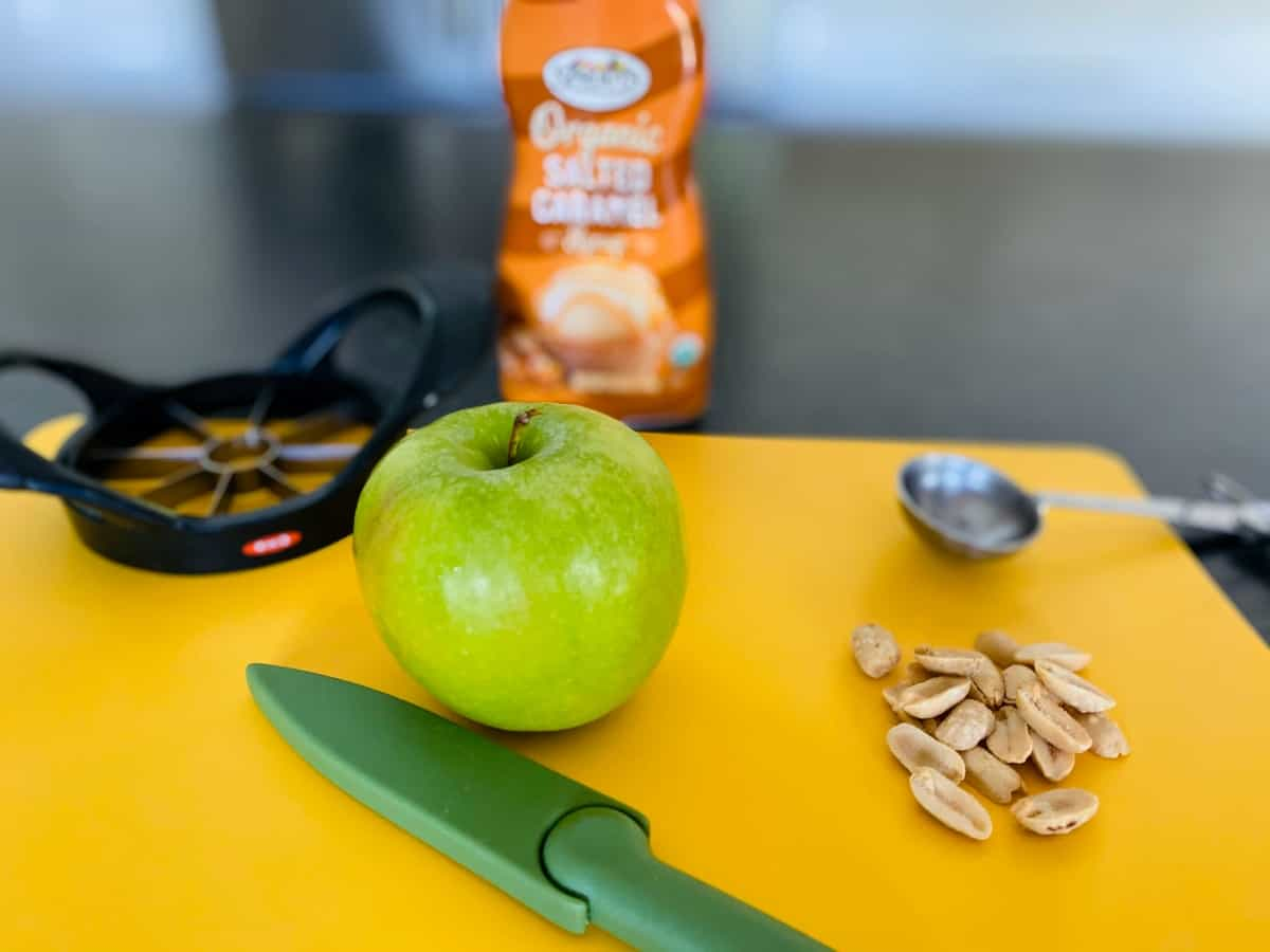Granny Smith apple, peanuts, caramel sauce, knife and apple corer on yellow cutting mat.