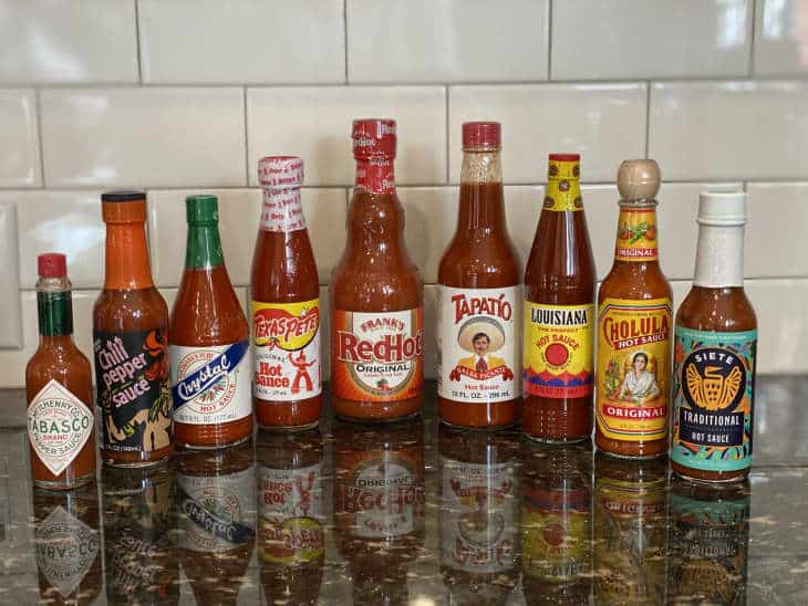 An assortment of bottled hot sauces on kitchen counter.