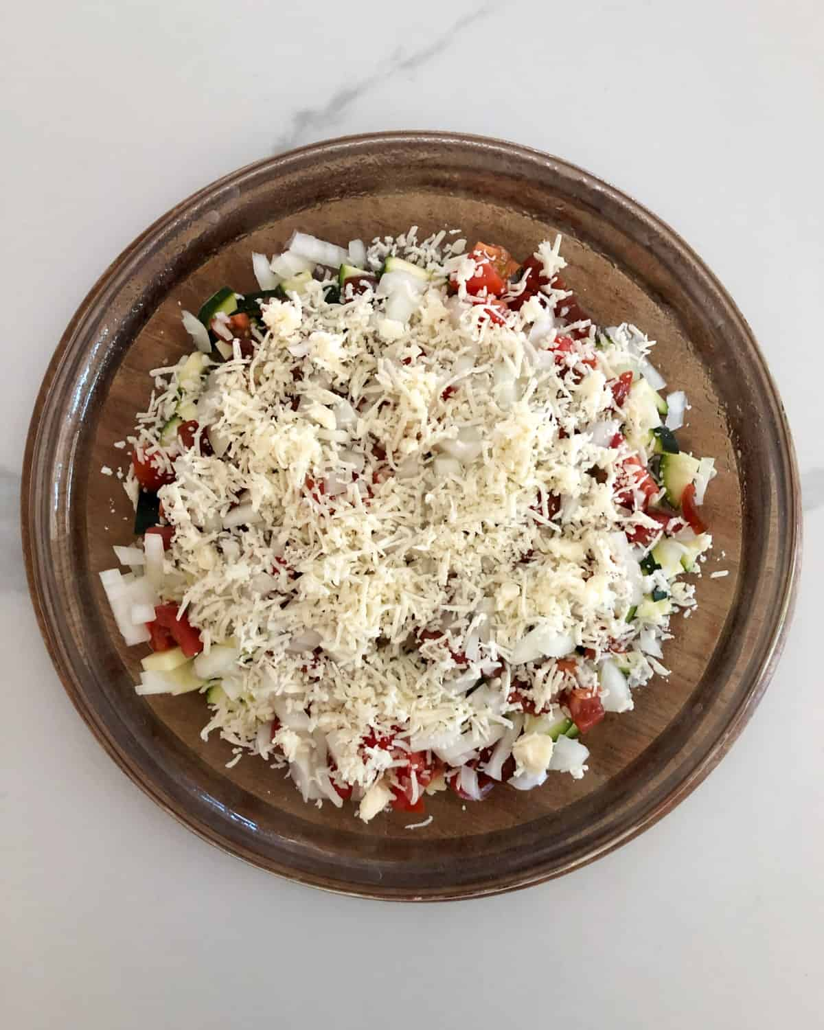 Glass pie dish layered with chopped zucchini, tomato, onion and grated cheese.