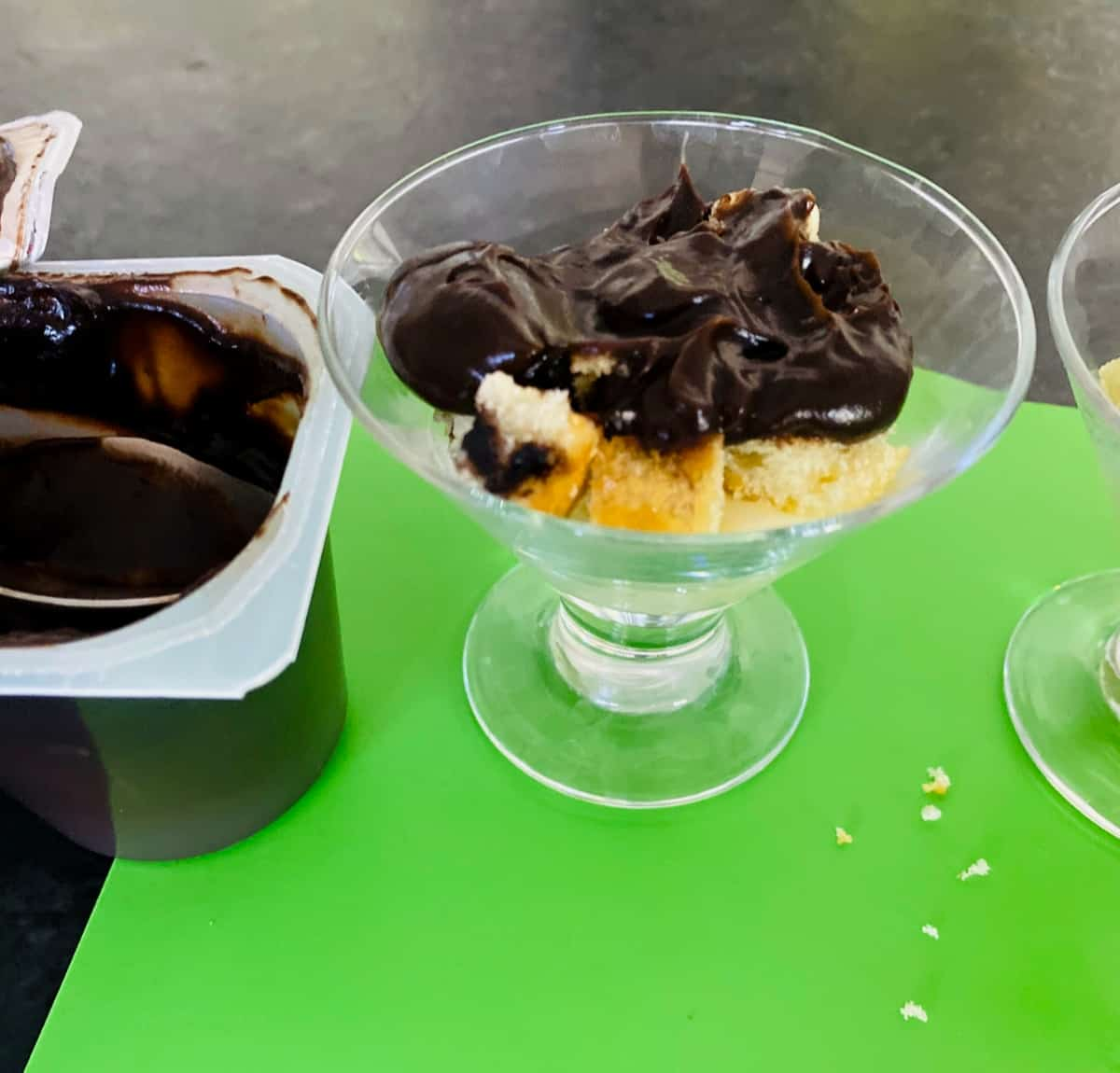 Stemmed dessert glass with vanilla pudding, VitaTops muffin top pieces and chocolate pudding on green mat.