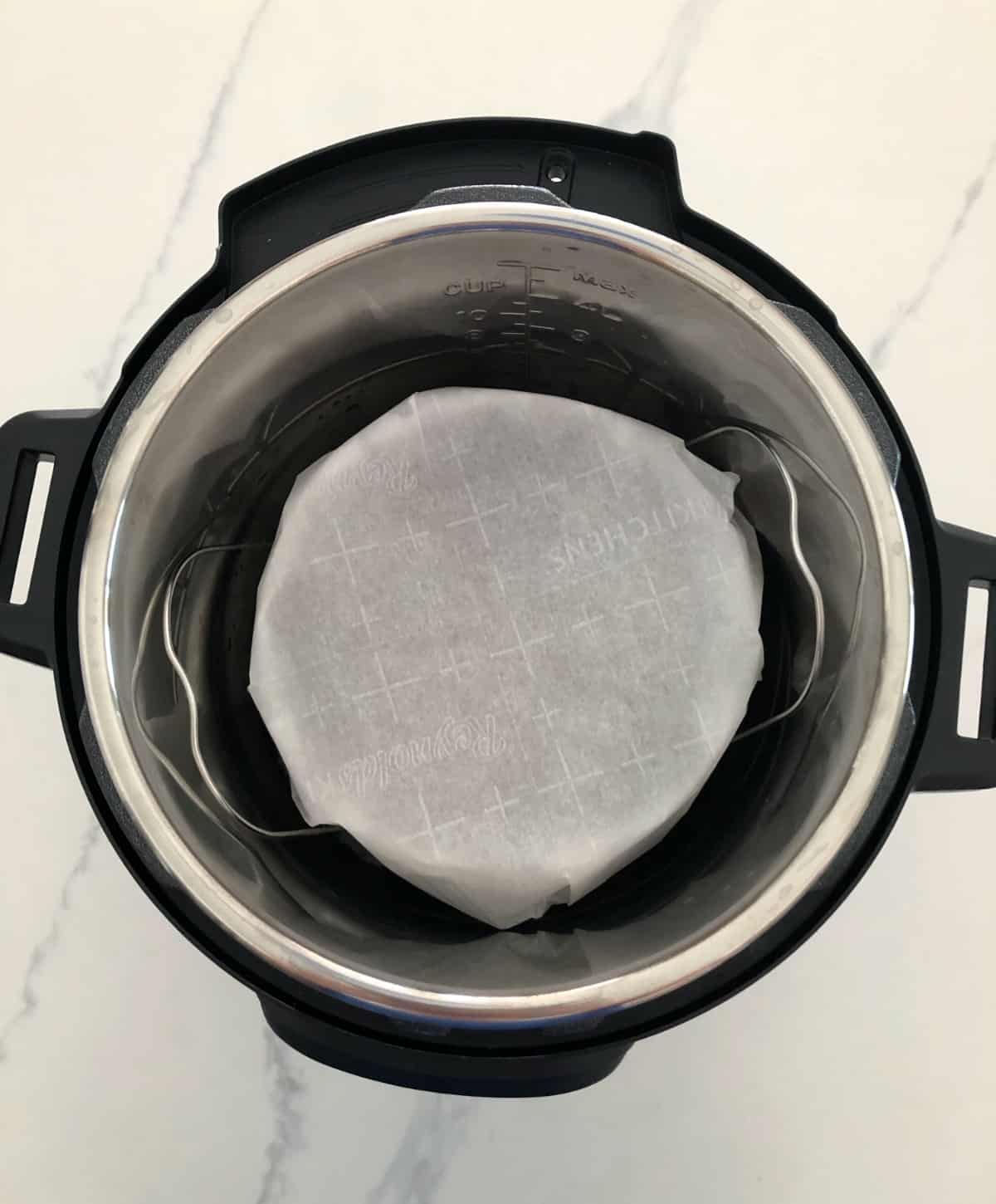 Parchment covered cookie pan on trivet in Instant Pot.