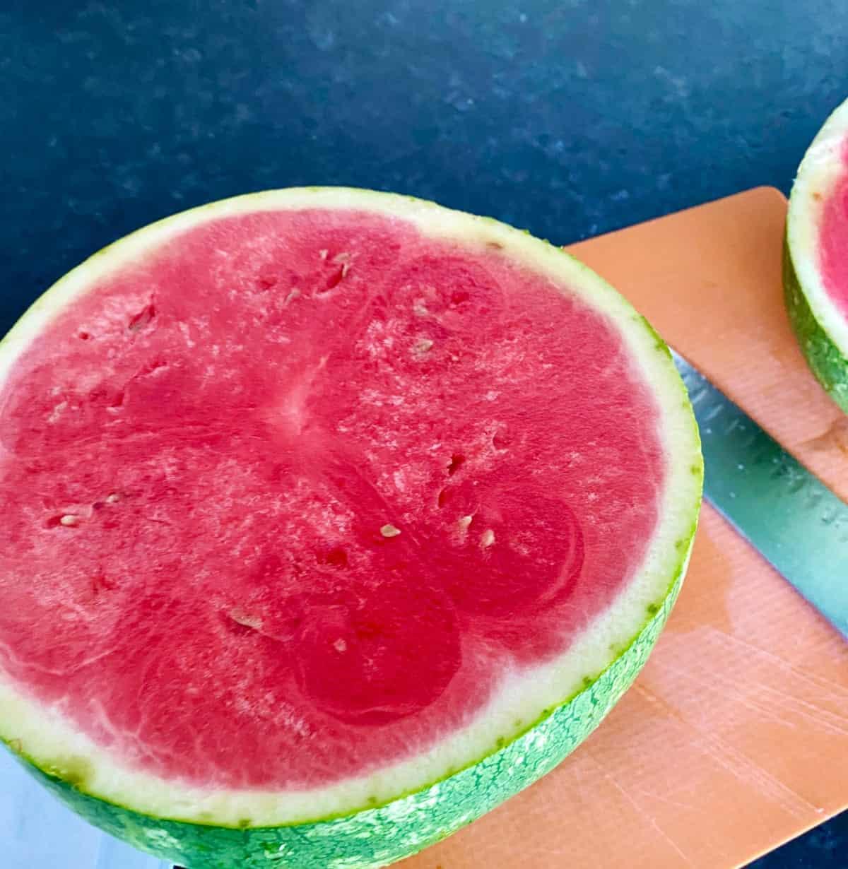 Plain slice of watermelon on orange cutting mat with knife.