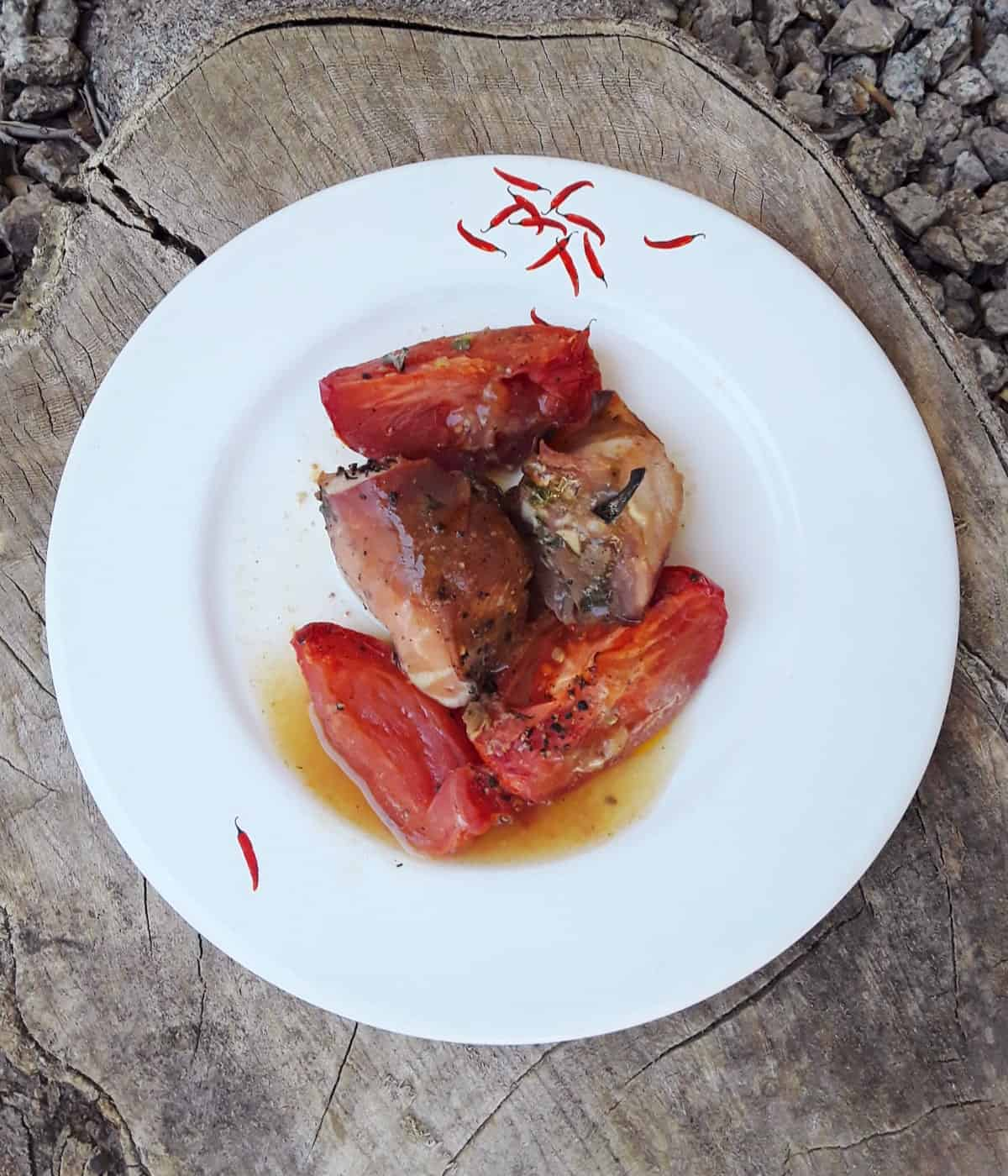 Prosciutto wrapped chicken with tomatoes on white dinner plate with wood and stone background.