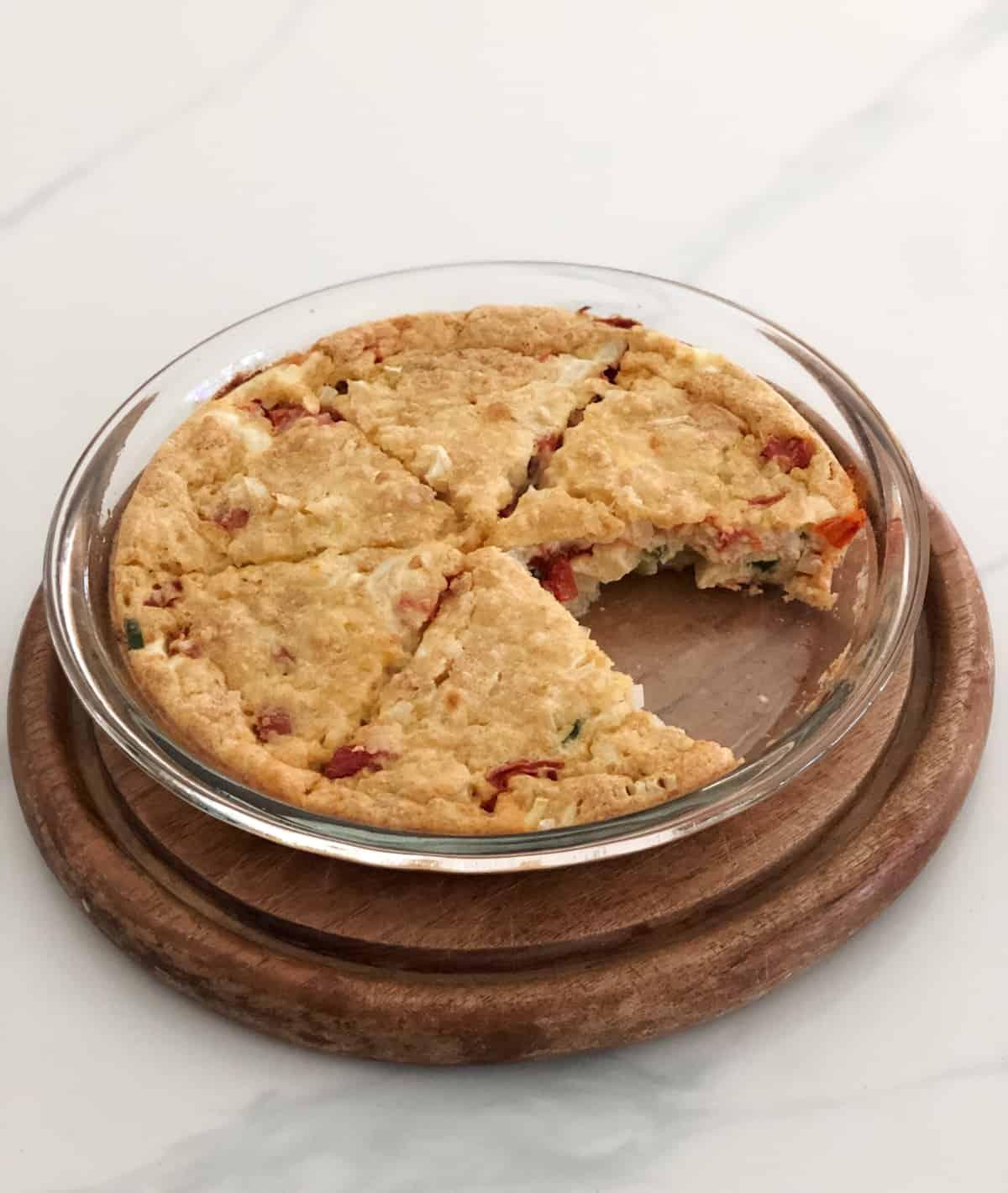 Zucchini pie in glass pie dish cut into six wedges.