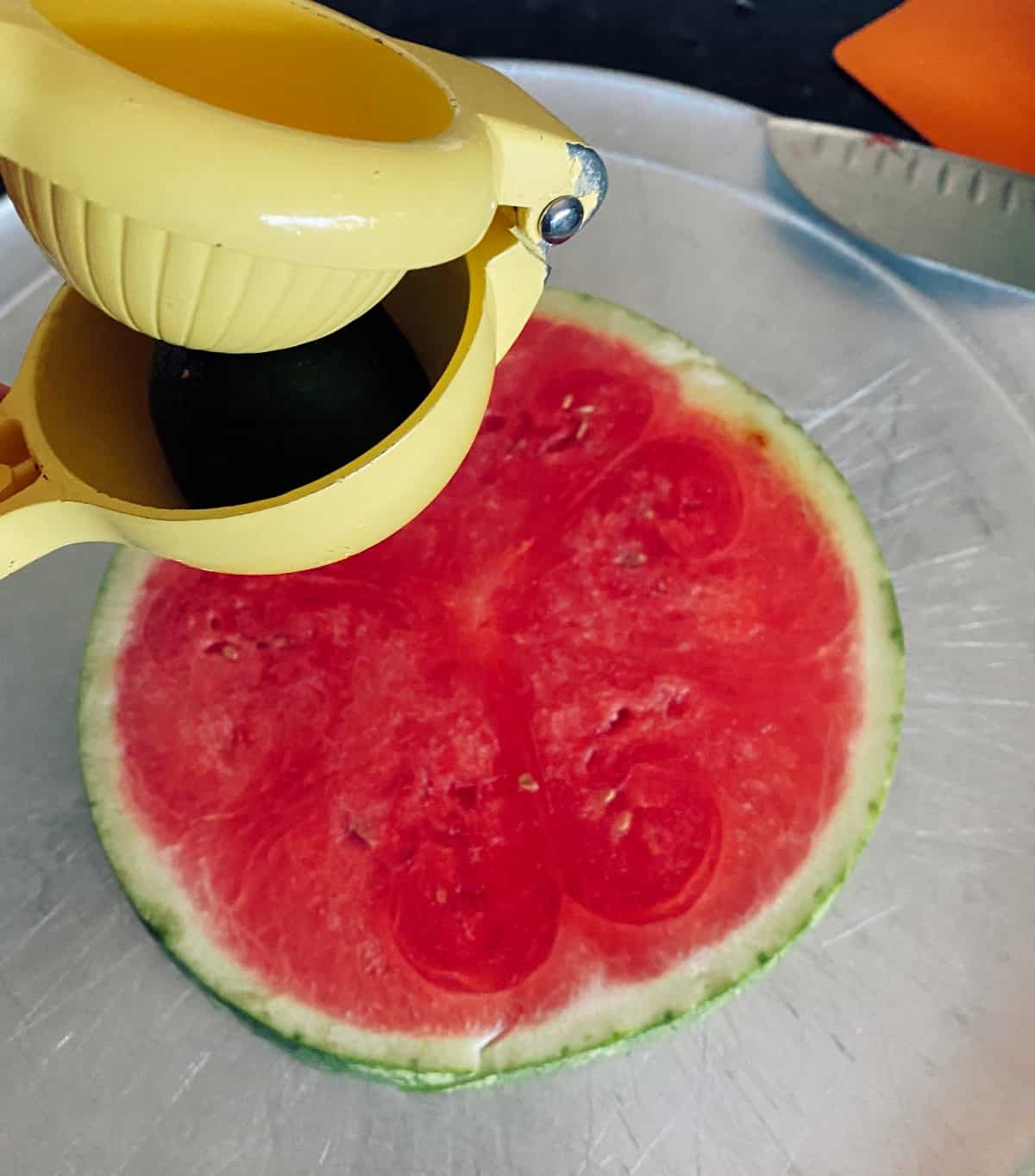 Squeezing lime juice over slice of watermelon.