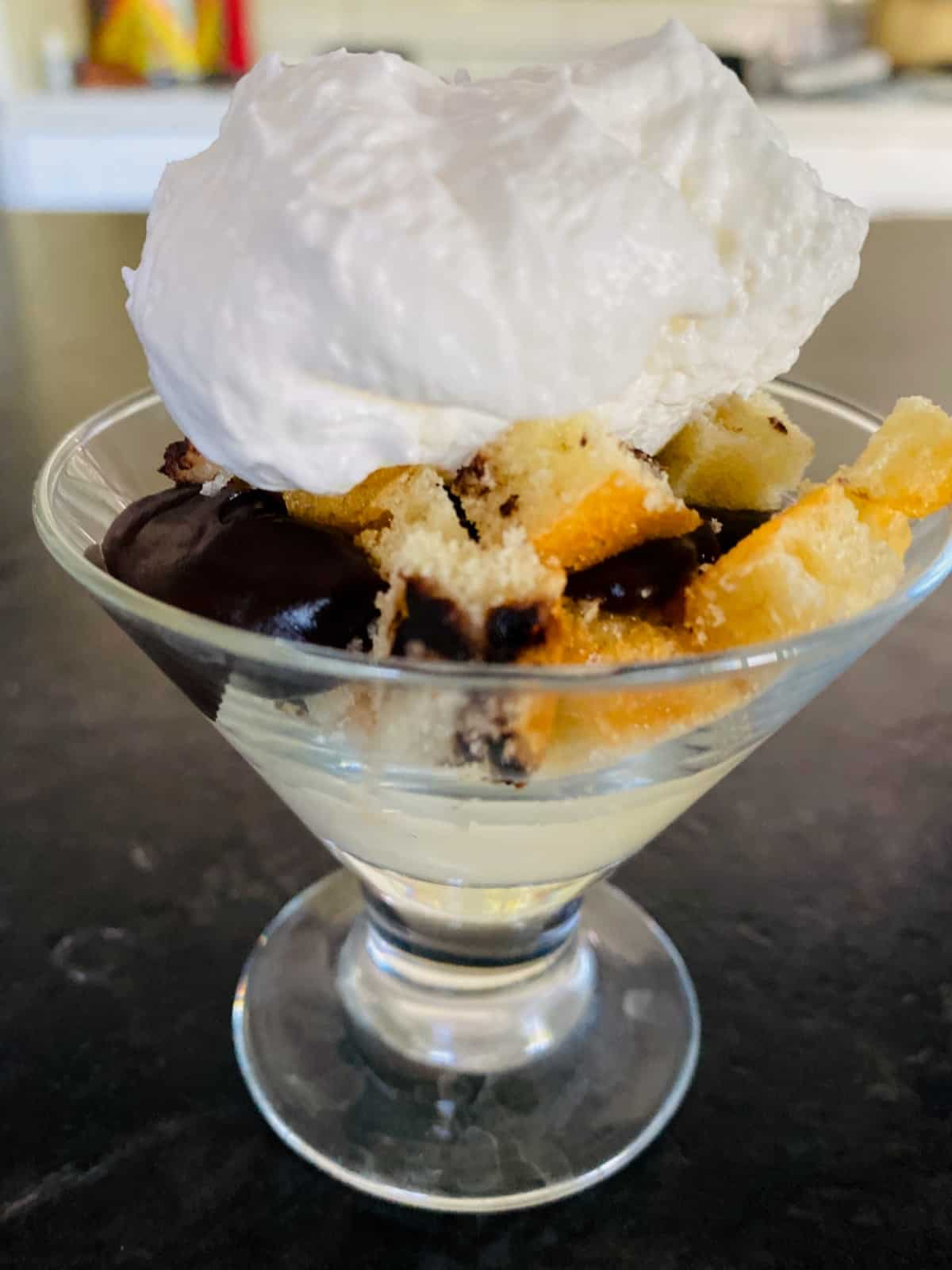 Stemmed dessert glass trifle with vanilla pudding, chocolate pudding, VitaTops muffin pieces and whipped topping on black countertop.