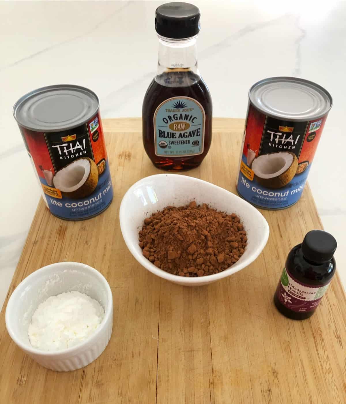 Agave nectar, lite coconut milk, cocoa powder, cornstarch and vanilla extract on bamboo cutting board.