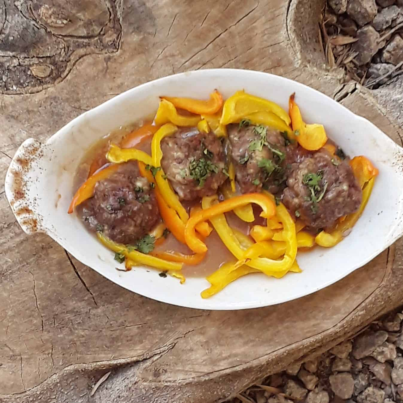 Baked meatballs with peppers in white baking dish.