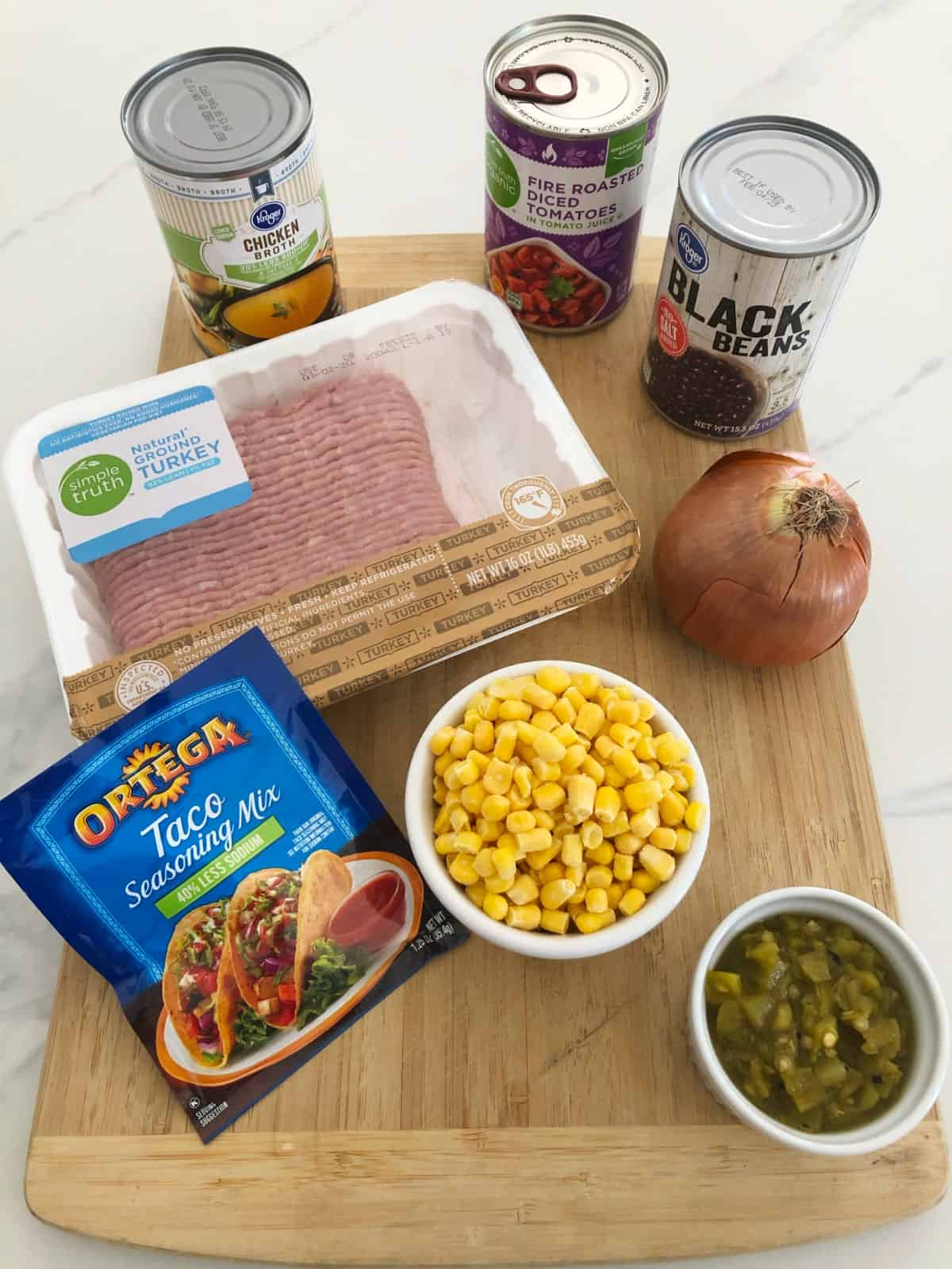 Cans of chicken broth, diced tomatoes and black beans with ground turkey, corn, green chiles, onion and taco seasoning on cutting board.