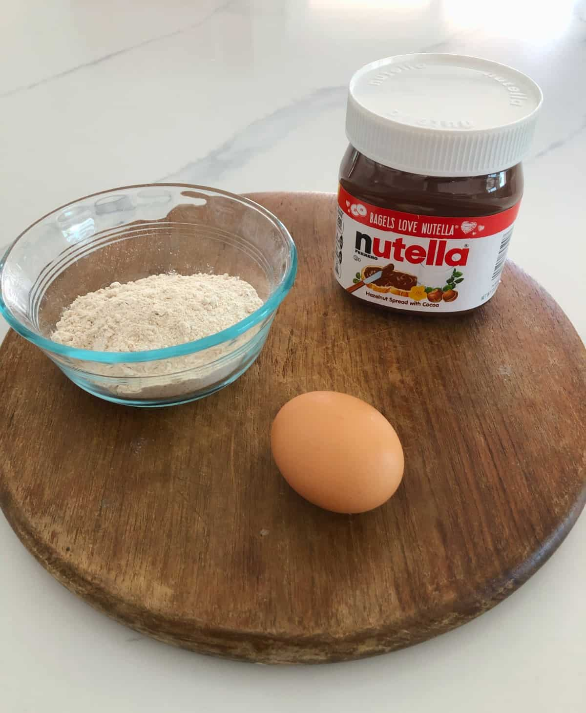 Jar of Nutella, all-purpose flour and an egg on round wood cutting board.