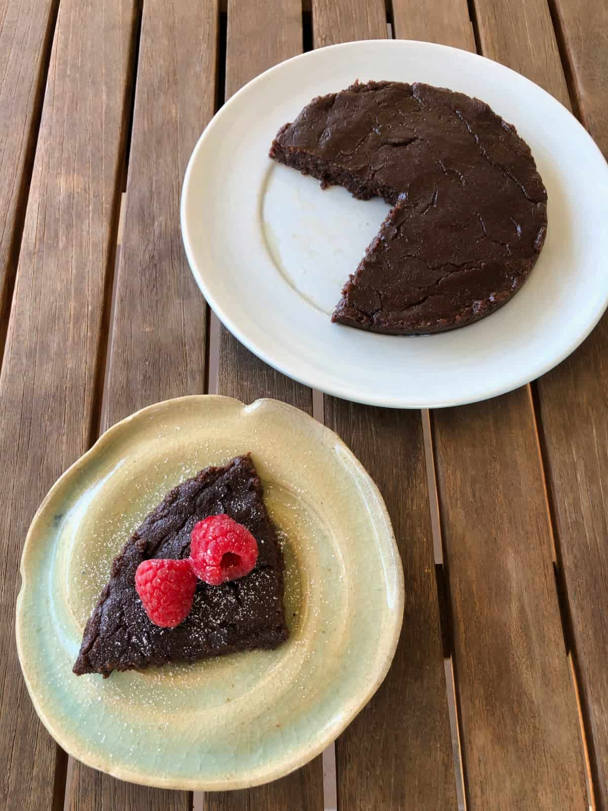 Easy 3-ingredient Nutella Fudge cake on plate near piece of cake topped with fresh raspberries.