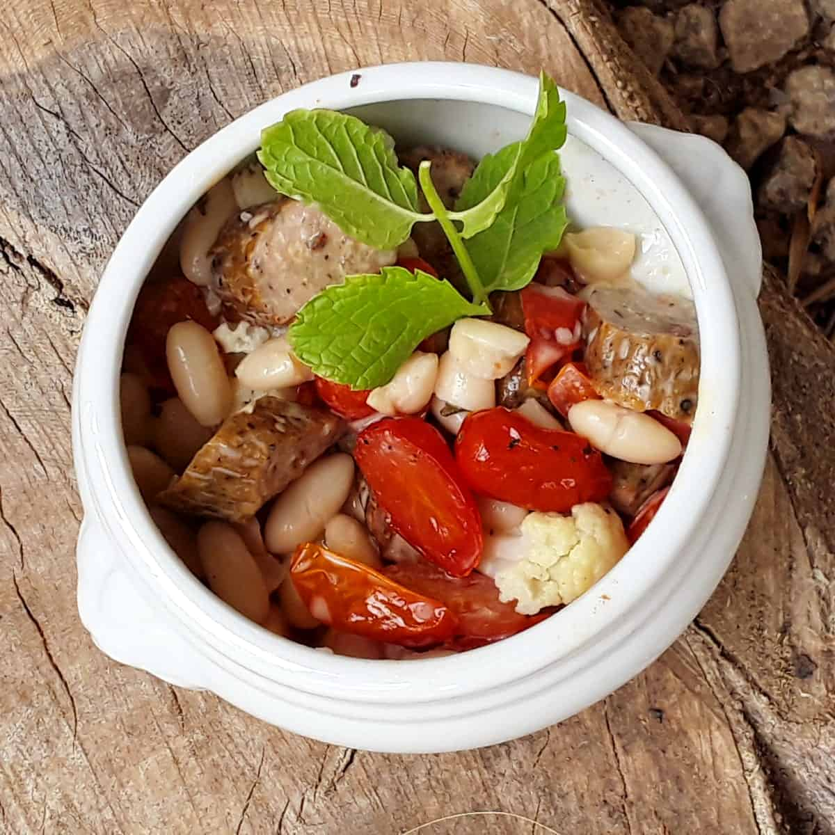 Sausage and tomatoes with white beans in small white bowl with fresh basil.