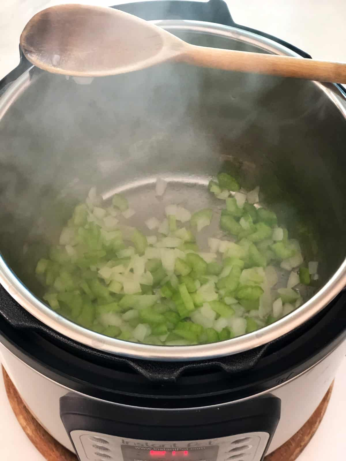 Sauteeing chopped celery and onion in Instant Pot.