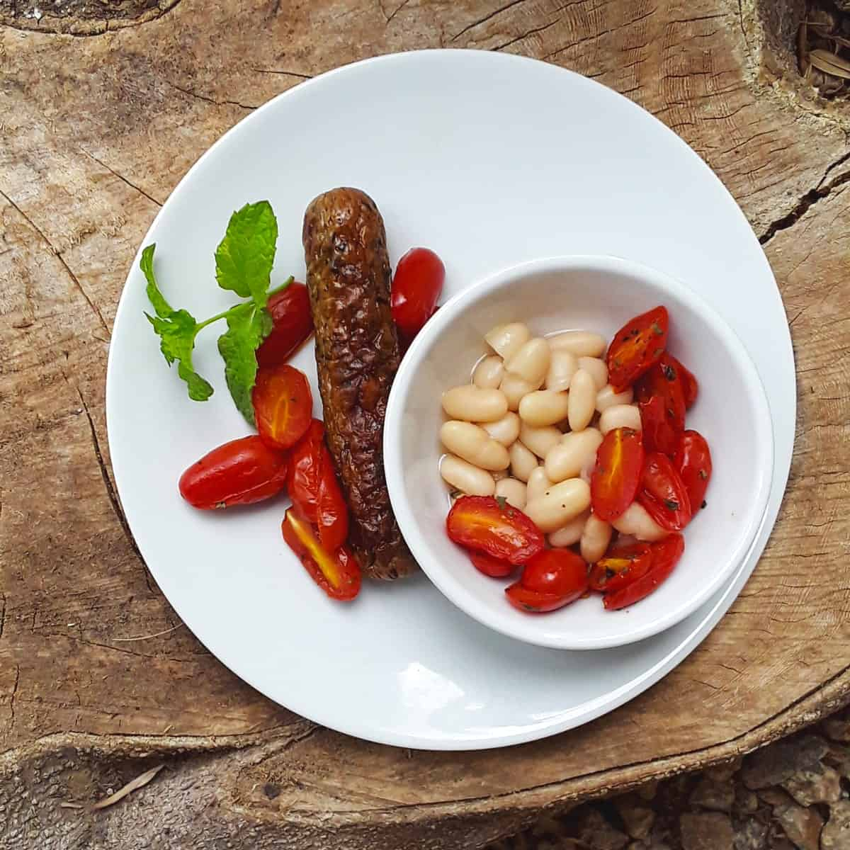 Spicy sausage with tomatoes and side of white beans on white plate.
