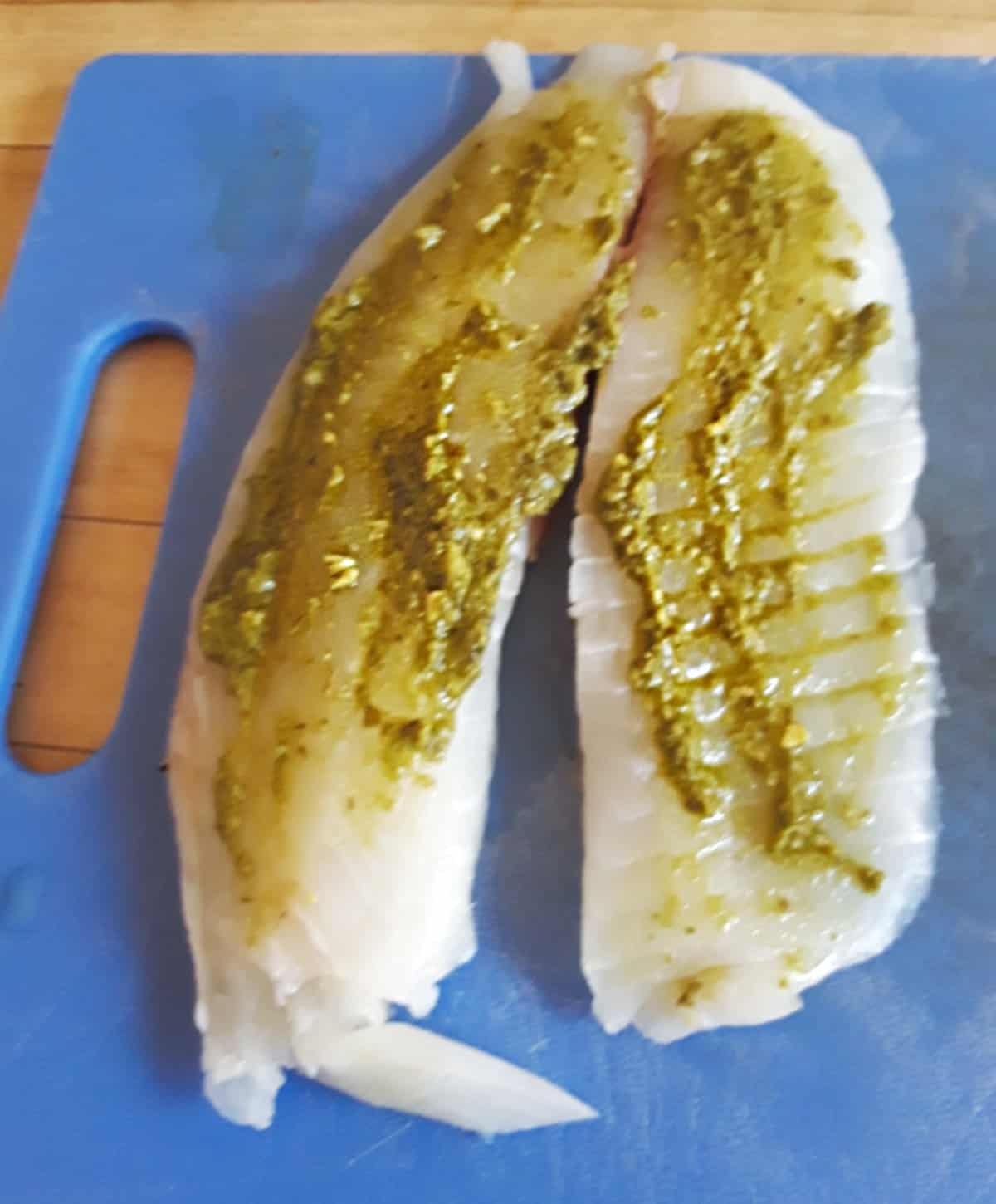Uncooked tilapia fillets topped with basil pesto on blue cutting board.