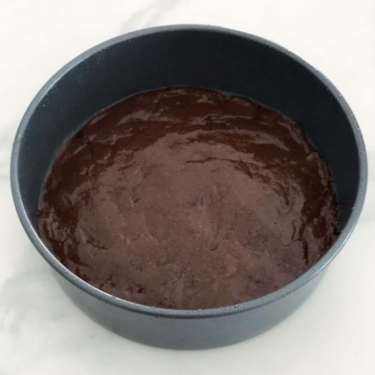 Unbaked Nutella cake in round cake pan.
