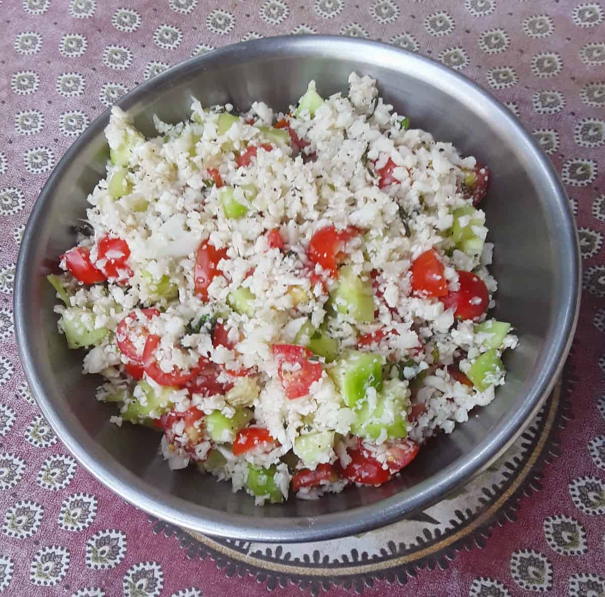 Cauliflower rice mixed with chopped cucumber and tomatoes in mixing bowl.