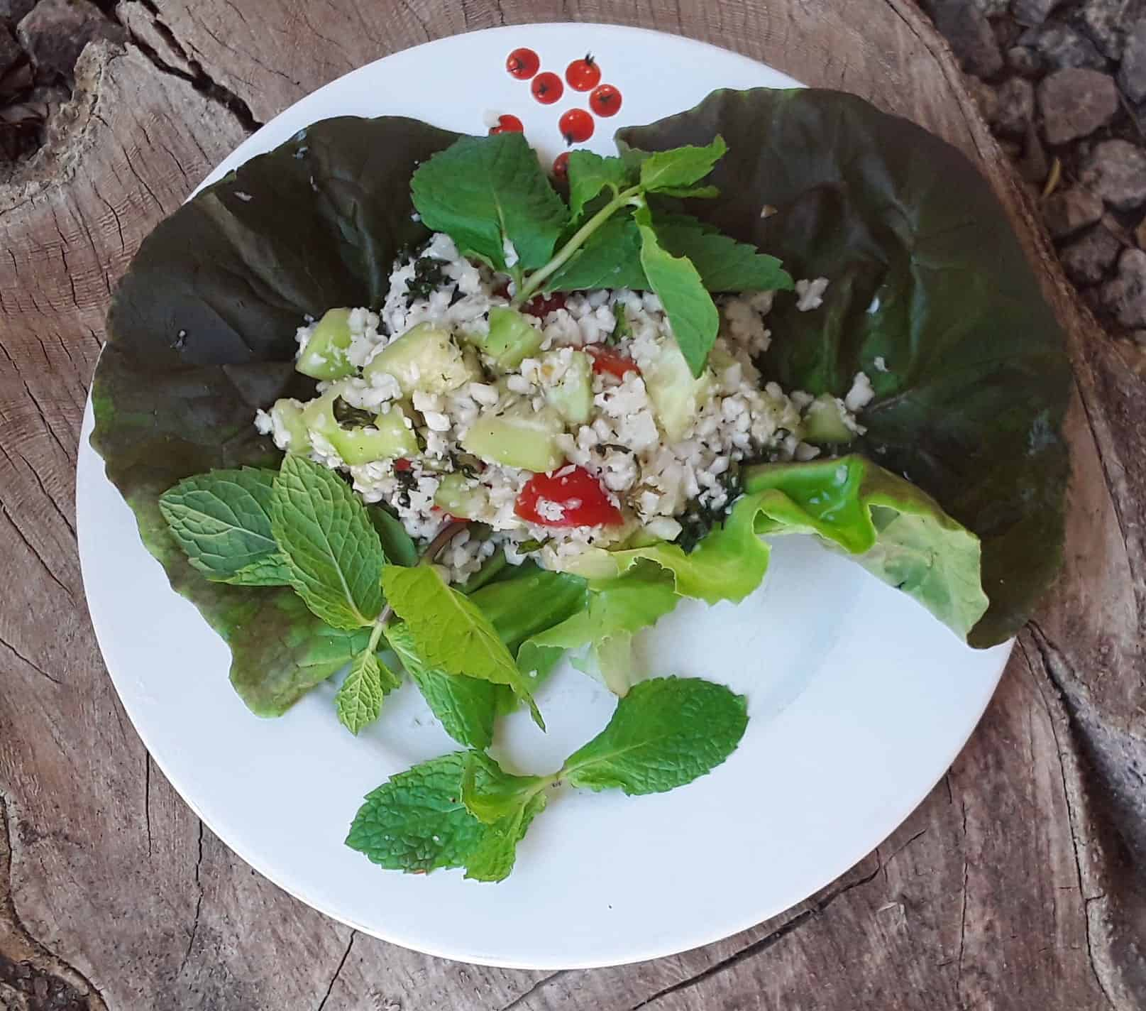 Cauliflower tabbouleh salad on lettuce leaves with fresh mint.