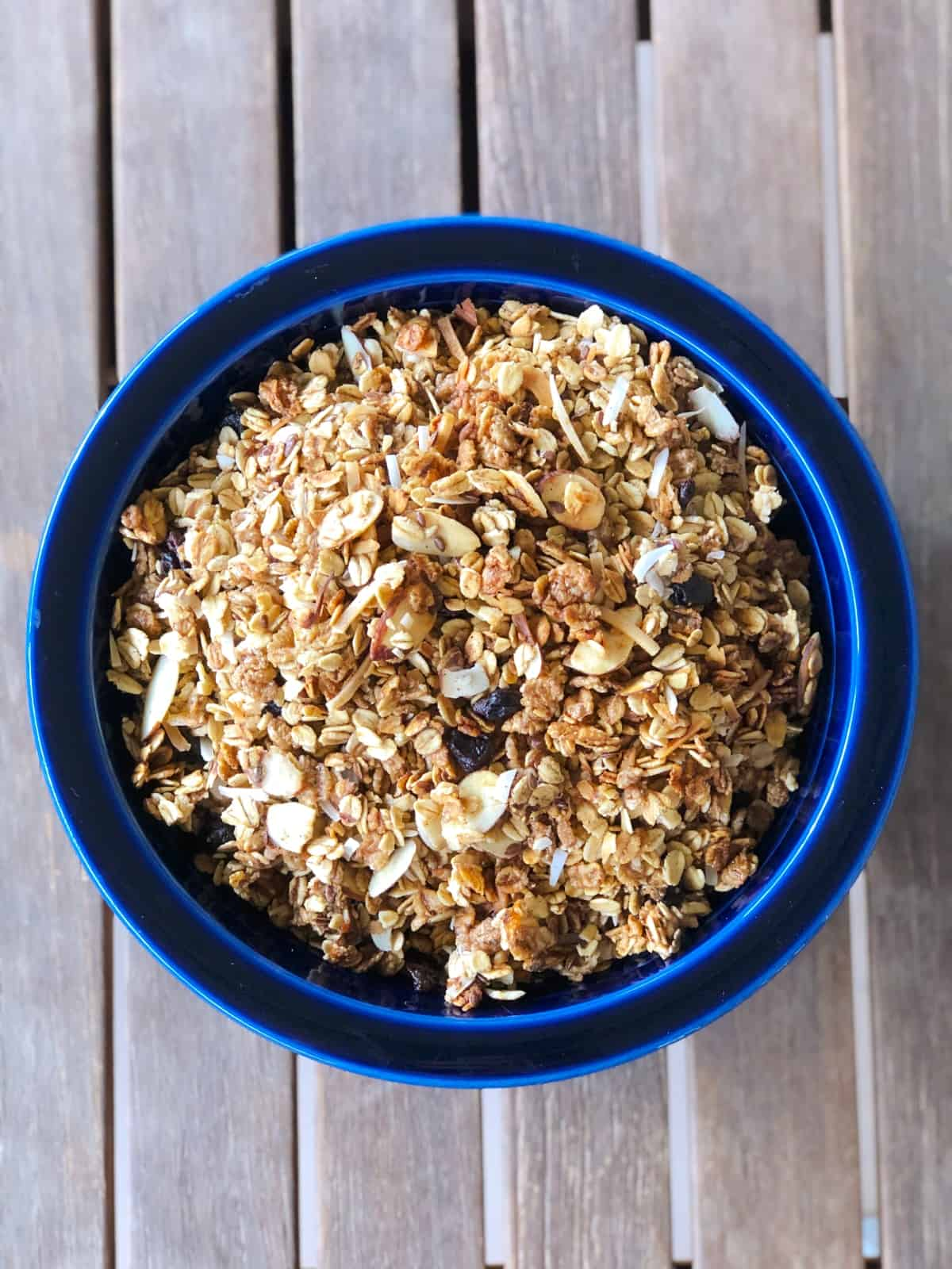 Homemade almond granola in blue bowl on wooden table.