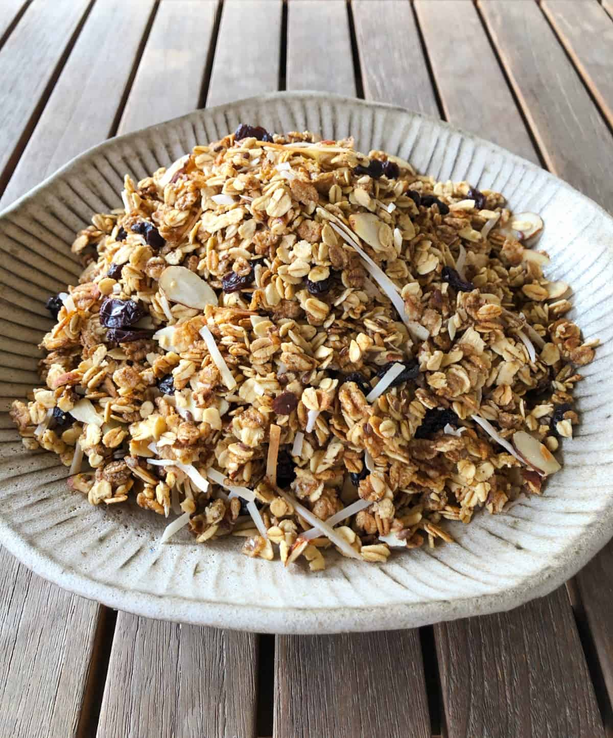 Homemade almond granola ceramic bowl on wooden table.