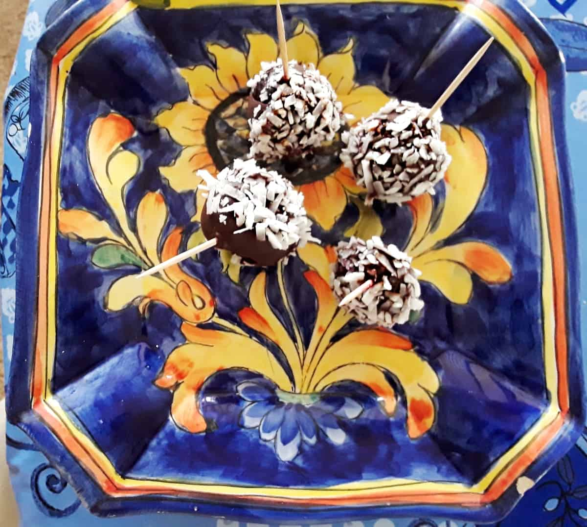 Chocolate covered cherries rolled in coconut on blue ceramic plate.
