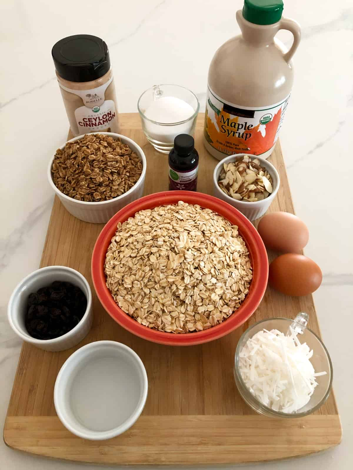 Cinnamon, maple syrup, oats, raisins, eggs, almonds and oil for making homemade granola.