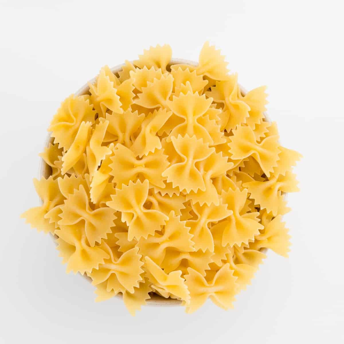 Dry uncooked farfalle pasta in small bowl from above.