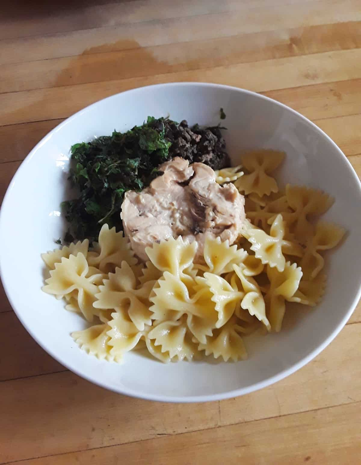 White bowl with cooked farfalle pasta, canned tuna, olive tapenade and fresh herbs before mixing.