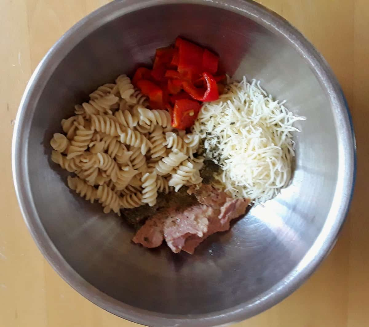 Fusilli pasta, red pepper, tuna and mozzarella in mixing bowl.