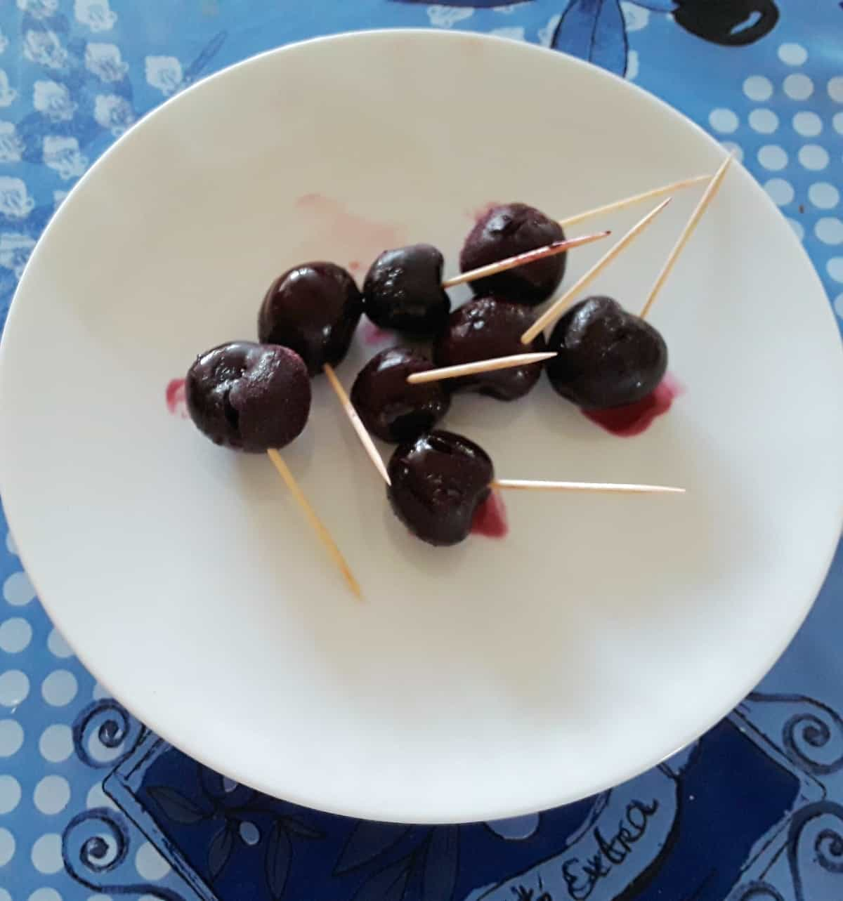 Thawed cherries skewered with toothpicks on white plate.