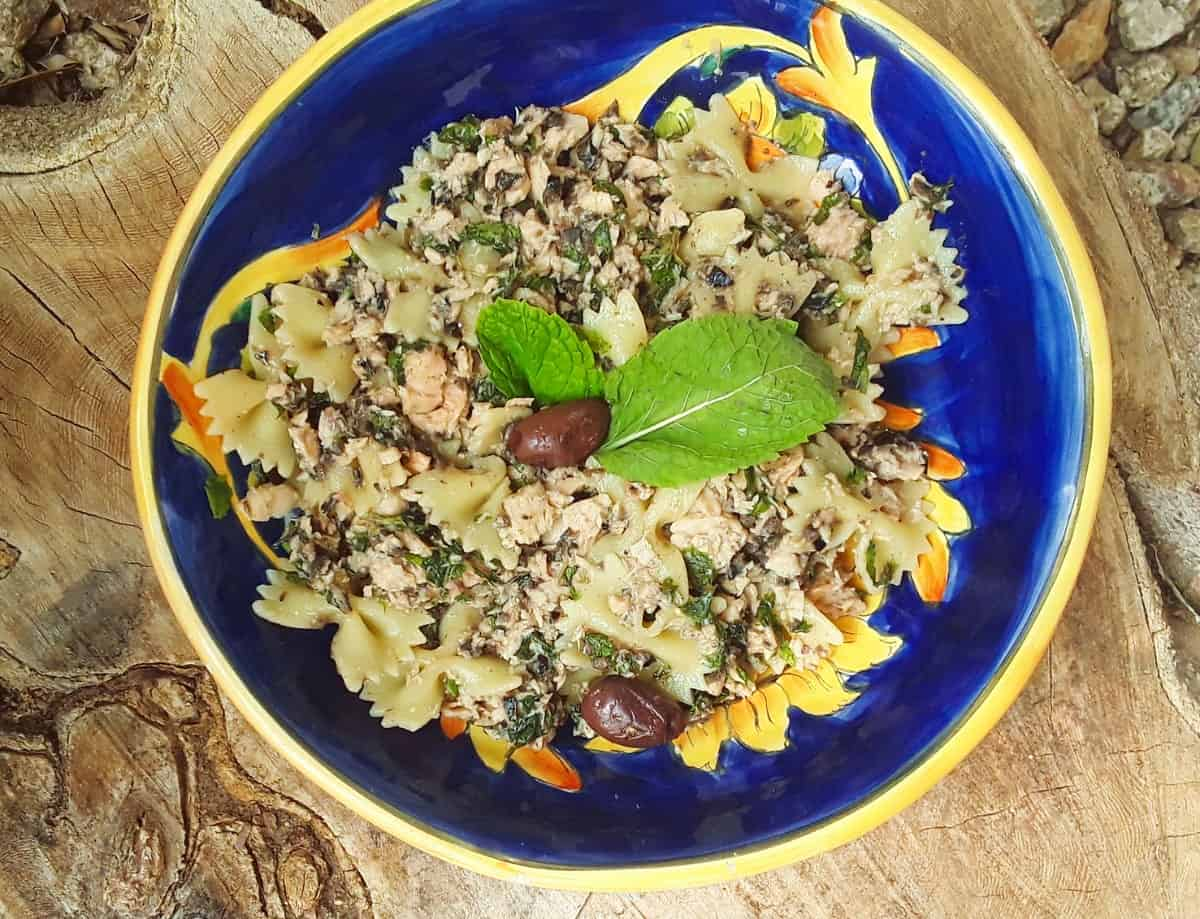 Tuna Pasta Tapenade Salad garnished with fresh mint leaves on blue ceramic plate.