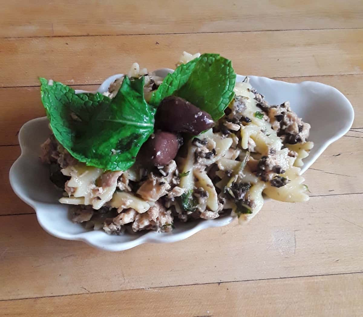 Tuna pasta tapenade salad garnished with fresh mint leaves in white dish on wood table.