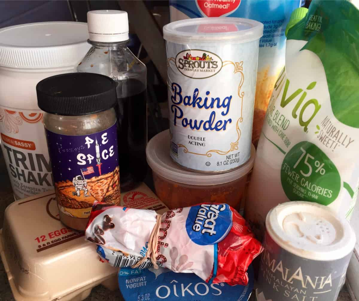 Ingredients for baking including baking powder, pie spice, Truvia, eggs, vanilla and Greek yogurt.