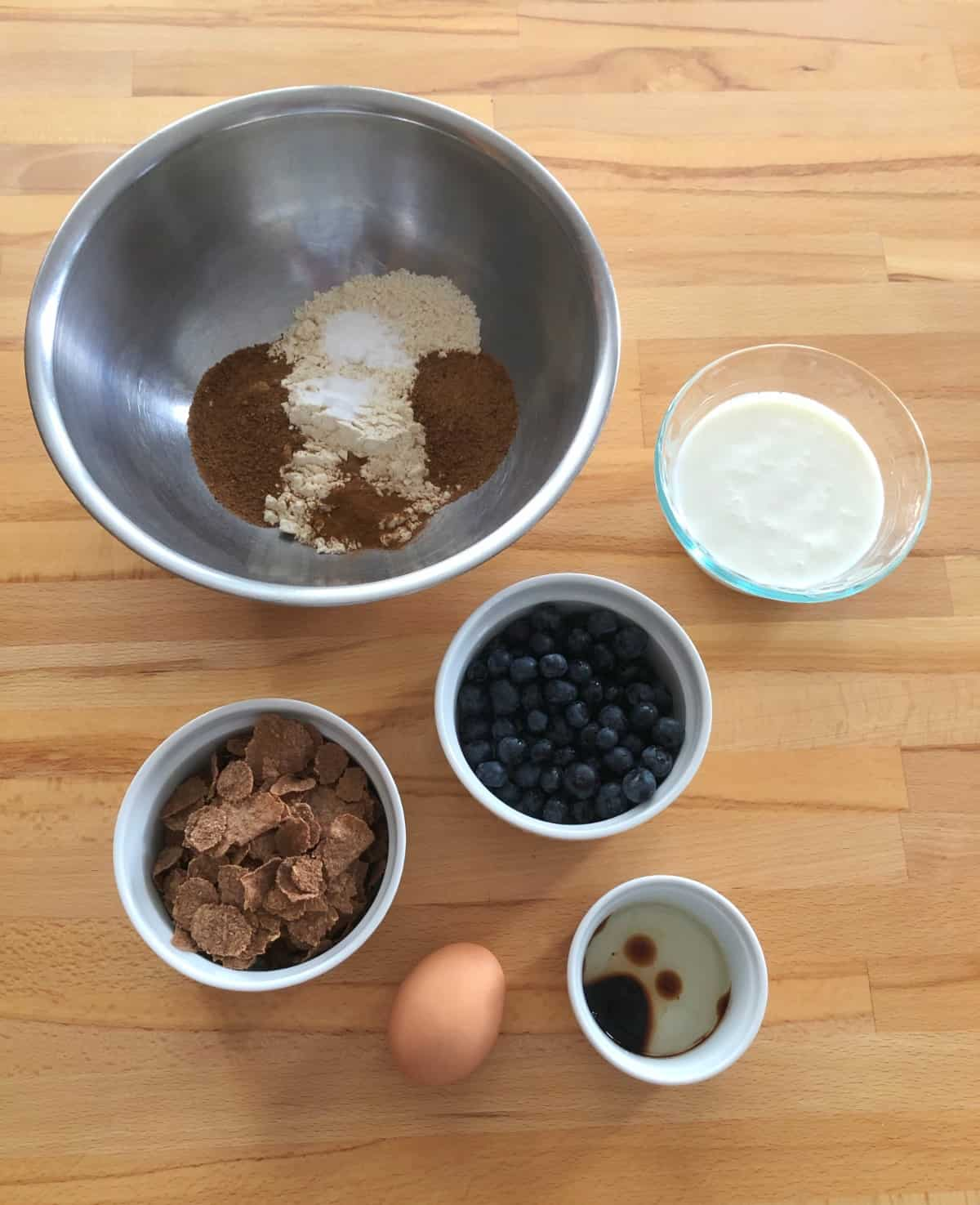 Bran flakes, blueberries, egg, buttermilk, oil, vanilla and flour mixture in separate bowls on wooden table.