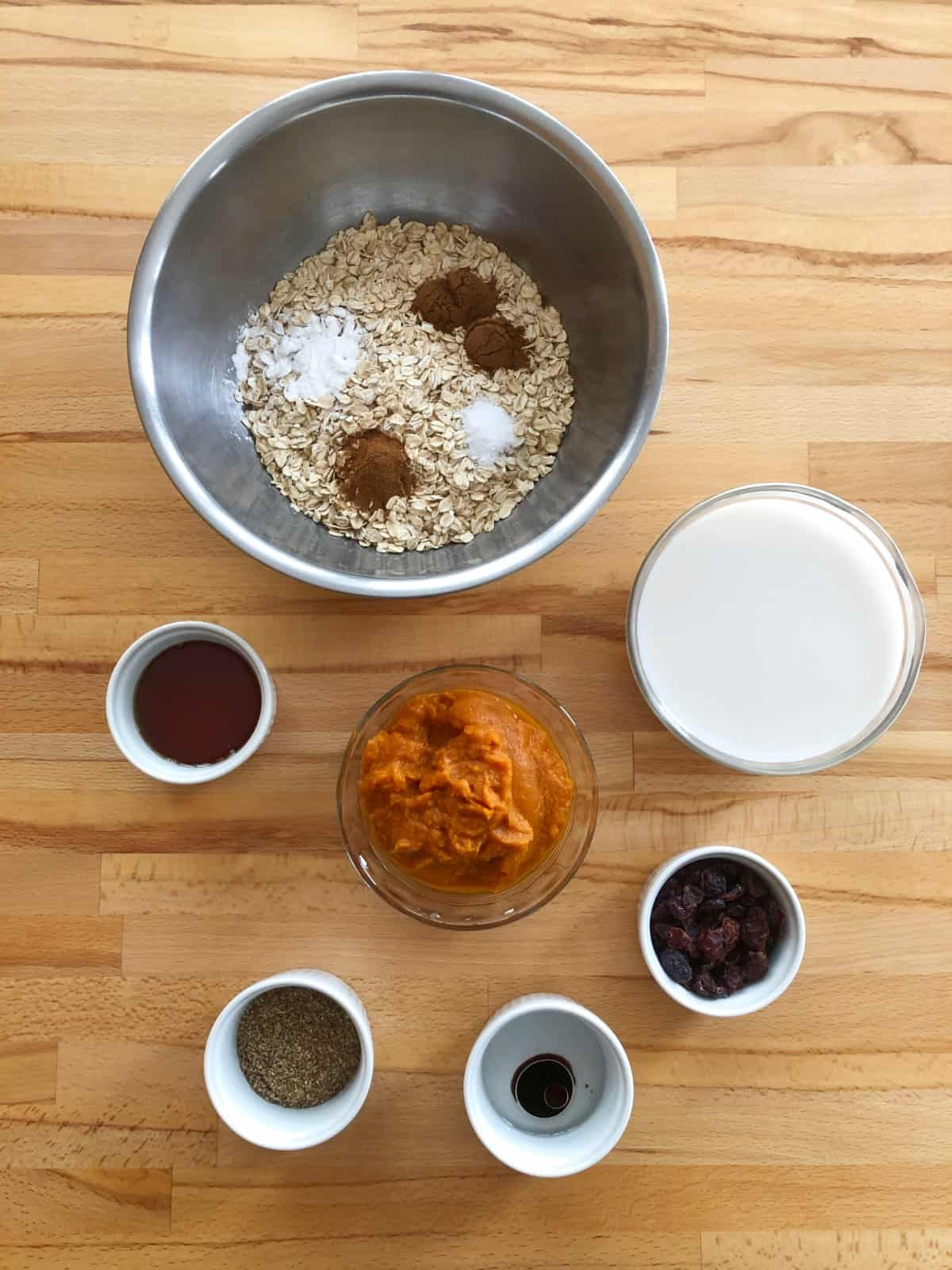 Mixing bowl with dry oats, cinnamon and salt, almond milk, maple syrup, pumpkin puree, dried cranberries and coconut oil for baking.