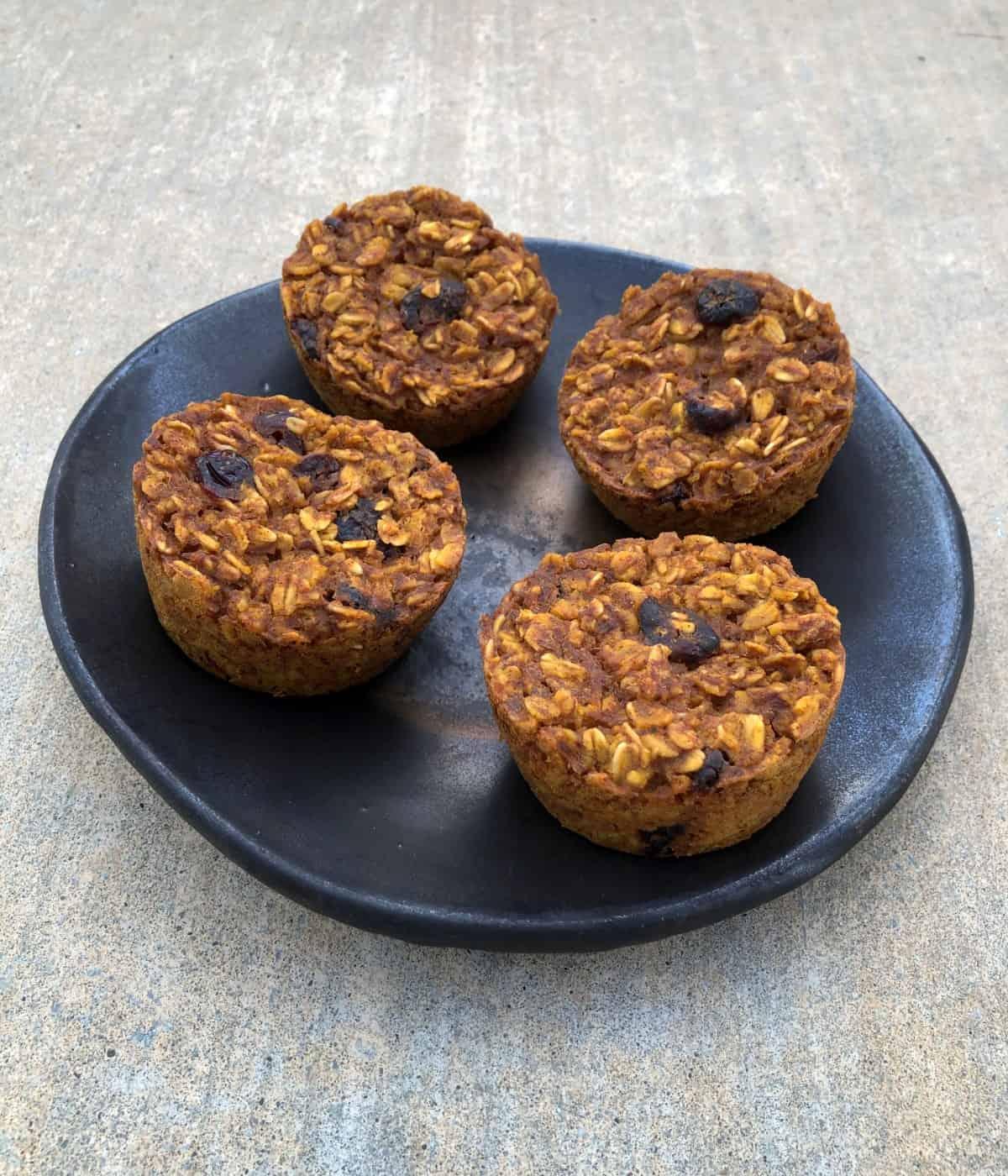 Pumpkin oatmeal muffin cups on brown ceramic plate.