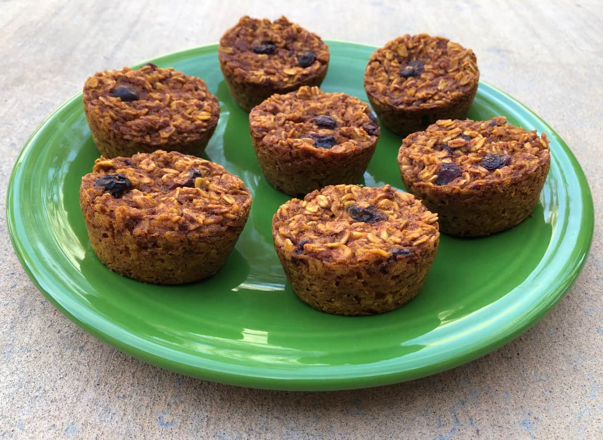 Pumpkin oatmeal muffin cups with dried cranberries on green serving plate.