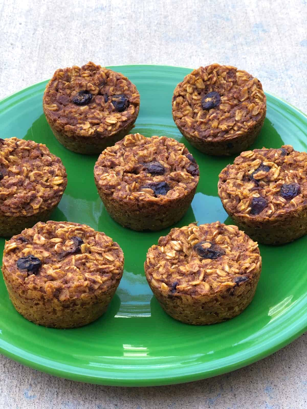 Freshly baked cranberry pumpkin oatmeal muffin cups on green plate.