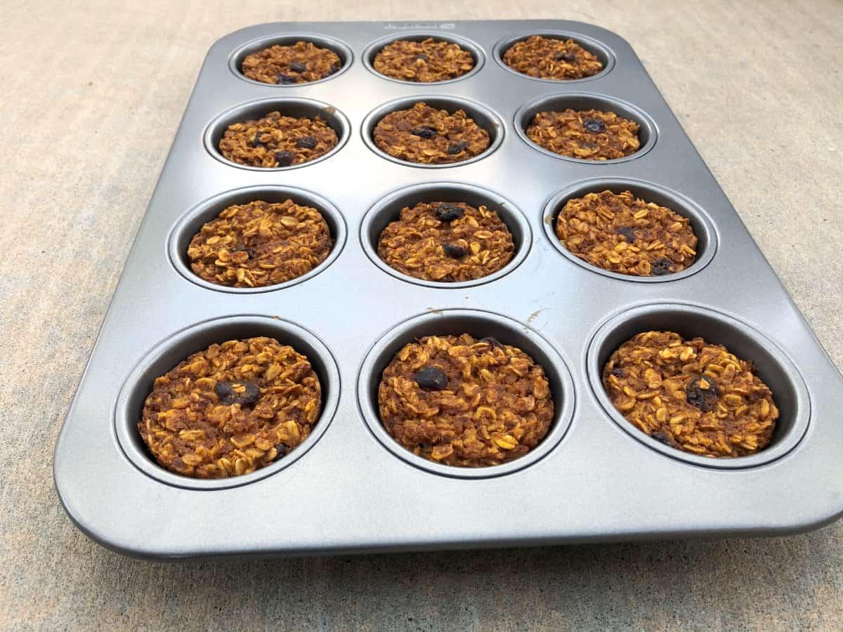 Fresh baked pumpkin oatmeal muffin cups in muffin pan.