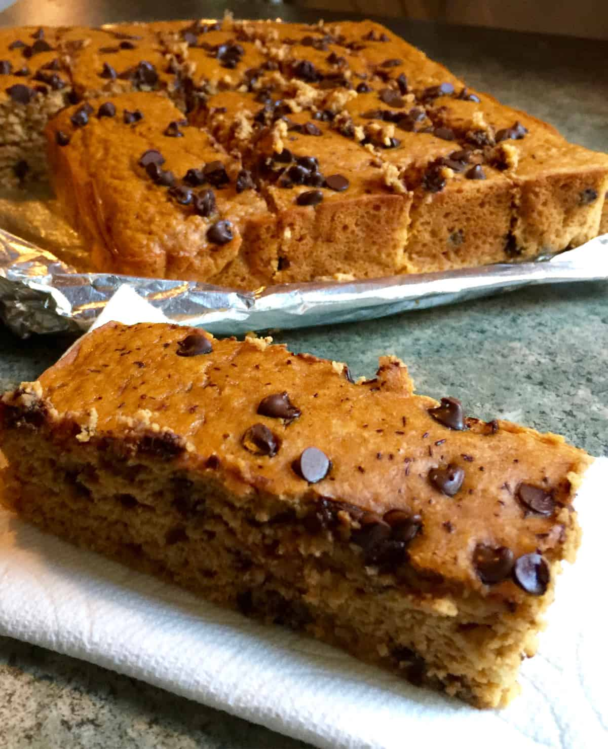 Pumpkin Chocolate Chip Blondie sitting in napkin in front of pan of blondies.