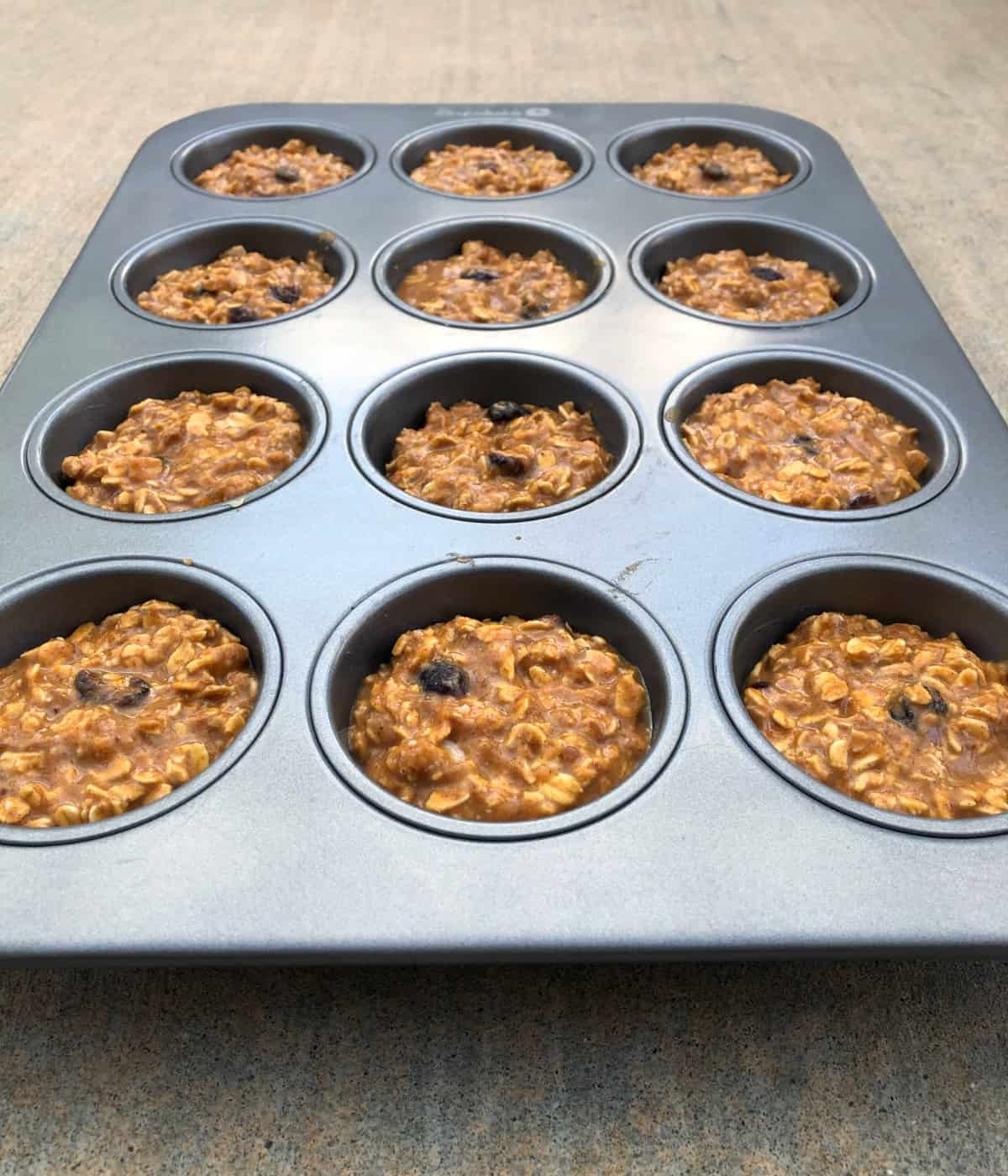 Unbaked pumpkin oatmeal muffin cups with dried cranberries in muffin pan.