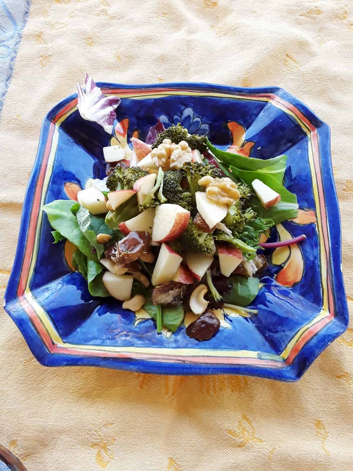Broccoli apple walnut salad topped with chopped dates on a blue ceramic plate.