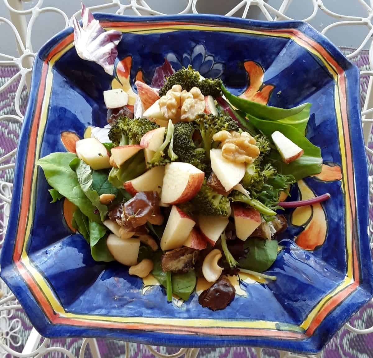 Salad with chopped cooked broccoli, chopped apple, walnuts and dates on a bed of mixed greens in blue ceramic plate.