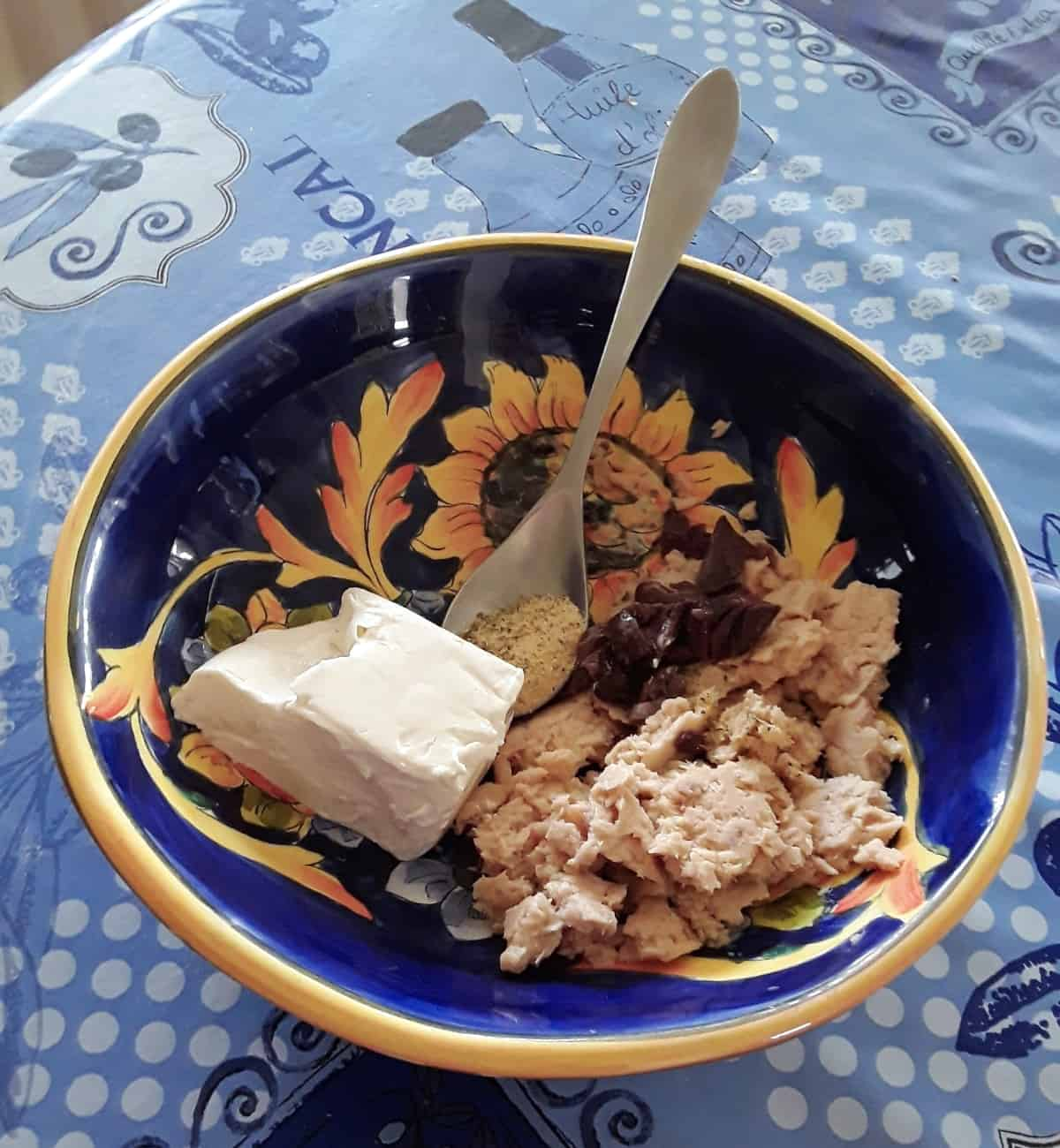 Cream cheese, tuna, olives and seasoning in blue mixing bowl with spoon.