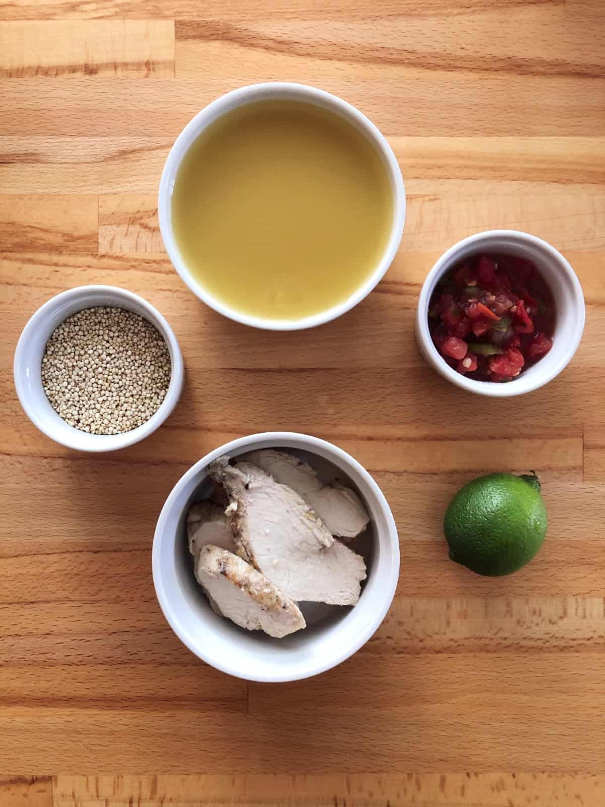 Uncooked quinoa, chicken broth, cooked chicken breast, pico de gallo and fresh lime for making a mug of soup.